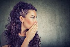 Woman whispering a gossip on gray background stock photos