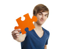 I have the solution. Young man holding a puzzle piece isolated on white background, soluton concept Stock Image
