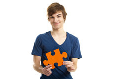 I have the solution. Young man holding a puzzle piece isolated on white background, soluton concept Stock Photography