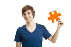 I have the solution. Young man holding a puzzle piece isolated on white background, soluton concept Stock Photos