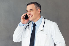 I have some great news for you!. Mature male doctor talking on mobile phone with smile while standing against grey background royalty free stock photos
