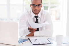I have some paperwork for you!. Confident young African man in shirt and tie stretching out documents and looking at you while sitting at his working place royalty free stock photo