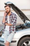 I have some road troubles. Serious young man talking on the mobile phone while leaning a vehicle hood royalty free stock photography