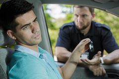 I have to ask for your car keys, sir. Shot of a resigned young driver giving his car keys to the policeman Royalty Free Stock Image