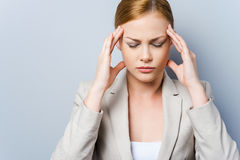 I have to concentrate. Depressed young businesswoman touching her cheekbone and keeping eyes closed while standing against grey background Stock Image