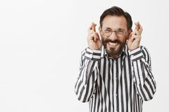 I have to win. Excited and nervous adult man with beard in formal clothes and glasses, raising fingers crossed. Clenching teeth, making wish, feeling worried Royalty Free Stock Image