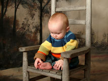 I Have Toes!. Baby playing with toes while sitting on a rustic chair Royalty Free Stock Images