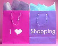 I Heart (Love) Shopping message on pink and purple shopping bags. Retail therapy, I love shopping, concept with colorful pink, blue and purple shopping bags Stock Images