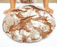 I hends della bambina si avvicinano al pane nero della Baviera fotografie stock