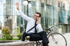 I am here!. Cheerful young businessman talking on the mobile phone and waving somebody while sitting near his bicycle with office building in the background Royalty Free Stock Image