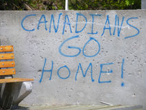 Quebec City Canada Political Graffiti, Canadians Go Home!, I Am Home, Québec City, Canada. Political graffiti found on a concrete wall, near a public bench stock photos