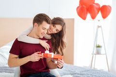 Loving girl congratulating her boyfriend at home Stock Photography