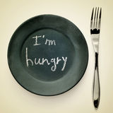 I am hungry. Picture of a fork and a plate painted as a blackboard with the text I am hungry written in it on a beige background with a retro effect royalty free stock photo