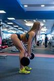 I idrottshall Nätt kvinna som gör squats med skivstången Royaltyfri Foto
