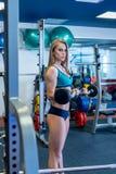 I idrottshall Sexig flicka som poserar, medan rymma hanteln Arkivfoto