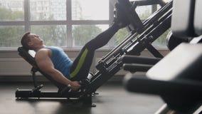 I idrottshallen - muskulös man som övar på benpressmaskinen Arkivbild