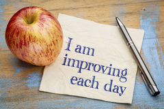 I am improving each day - napkin with apple. I am improving each day - self development concept or positive affirmation - handwriting on a napkin with an apple Royalty Free Stock Photos