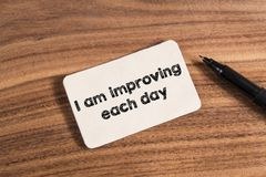 I am improving each day word. Write in card on wood background Royalty Free Stock Photo