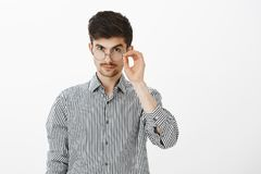I am intrigued. Handsome confident young caucasian male coworker, looking from under forehead with lifted eyebrow. Holding rim of glasses, being suspicious and royalty free stock photos