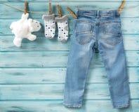 I jeans del neonato, i calzini ed il giocattolo bianco riguardano una corda da bucato fotografia stock libera da diritti