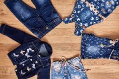 I jeans del ` s dei bambini, il rivestimento, gli shorts del denim ed il denim si vestono su fondo di legno Immagini Stock