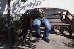 i jeans di taglio decorati con i fiori che si siedono su un giardino bench la a fotografia stock