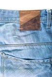 I jeans strutturano con l'etichetta su bianco immagine stock libera da diritti