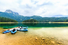 I kajak si sono messi in bacino sulla riva del lago nero Paesaggio della montagna, parco nazionale di Durmitor, Zabljak, Monteneg Immagini Stock Libere da Diritti