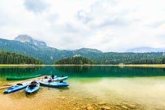 I kajak si sono messi in bacino sulla riva del lago nero, parco nazionale di Durmitor, Zabljak, Montenegro Fotografie Stock Libere da Diritti