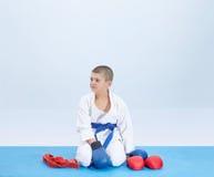 I karategi sitter idrottsman nen i karate poserar nära en dräktkarate Royaltyfria Bilder