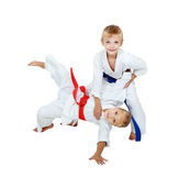 I kimono kastar pojken en flicka i en isolerad kimono Arkivbild