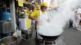 I kineskvarterområdet av Bangkok Thailand, på tillfället av det kinesiska nya året en kock som steker nudlar med en woka i gatan, arkivfilmer