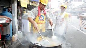 I kineskvarterområdet av Bangkok Thailand, på tillfället av det kinesiska nya året en kock som steker nudlar med en woka i gatan, stock video