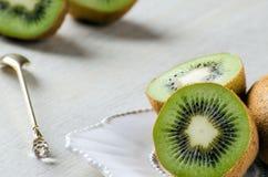 I kiwi su un cucchiaio bianco di dessert e del piatto Fotografia Stock