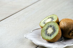 I kiwi sulla tavola su un piatto bianco Immagine Stock