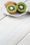 I kiwi sulla tavola su un piatto bianco Fotografie Stock Libere da Diritti