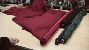 I klädlager fördelar representanten köparen rullen av den röda torkduken stock video