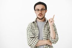 I know what do. Thrilled and amused smart stylish male in black beanie and glasses raising index finger in eureka. Gesture folding lips and staring energized stock photo