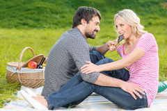 I know you like chocolate. Young men feeding his girlfriend with Royalty Free Stock Image