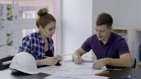 I konstruktionsföretag två arbetar teknikerer med teckningar på deras skrivbord lager videofilmer