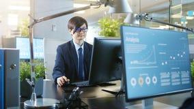 I kontoret arbetar att le den östliga asiatiska affärsmannen på ett skrivbord royaltyfri fotografi