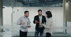 I kontorskorridor har arbetarna en konversation, en ung kvinnlig med ett kort hår som kommer med översikten till arbetarna lager videofilmer