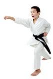 I kugge av karatepojken med en takt för svart bälte en stansmaskinarm Royaltyfri Foto