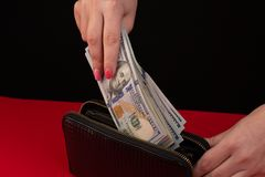 I kvinnor är händerna för ` s den svarta läderplånboken med en bunt av hundra dollar Affärserbjudande arkivfoto