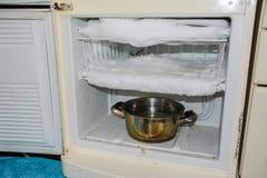 Is i kylen, behov som tinar, kylskåp som frysas arkivfoto