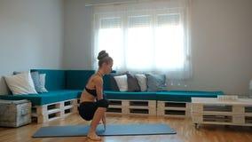 I lägenheten utför en kvinna squats med hennes händer ner arkivfilmer