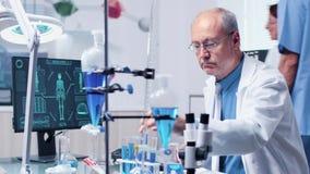 I laboratorium för modernt och högt slut ser doktorn i hans 60-tal olika rör med blåa prövkopior stock video