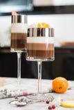 I lager chokladefterrätter i exponeringsglas Skivor av mandarinen på en överkant av sötsaken Selektivt fokusera Royaltyfri Fotografi