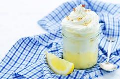 I lager efterrätt med citronkräm, glass och piskad kräm Arkivfoton