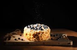 I lager kaka som dekoreras med bär och smulalögner på ett träbräde, idé för en kulinarisk katalog, svart bakgrund Royaltyfria Foton